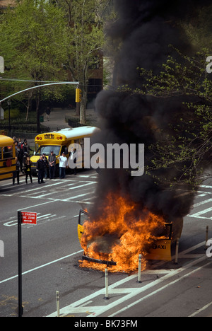 Members of the FDNY extinguish a taxicab that has caught fire on Ninth Avenue in the New York neighborhood of Chelsea - Stock Photo