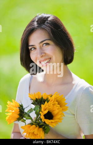 beautiful, young Hispanic woman in a grassy meadow holding flowers - Stock Photo