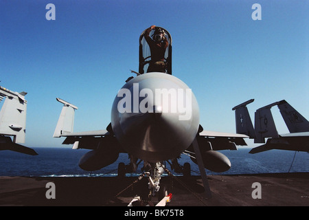 A naval pilot cleans and services an F-18A Hornet aboard the aircraft carrier USS Nimitz in the Persian Gulf, during - Stock Photo