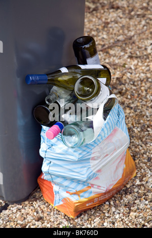 Empty glass wine bottles out for collection - Stock Photo