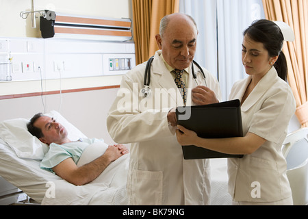 Patient in hospital with doctor and nurse - Stock Photo