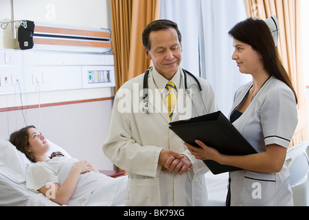 Young woman in hospital room with doctor and nurse - Stock Photo