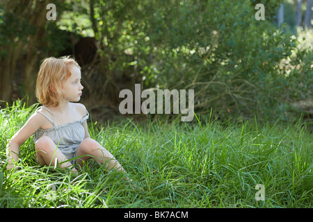Little girl sitting in grass - Stock Photo