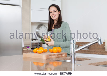 Young woman with oranges and orange juice - Stock Photo