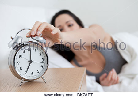 Young woman reaching for alarm clock - Stock Photo