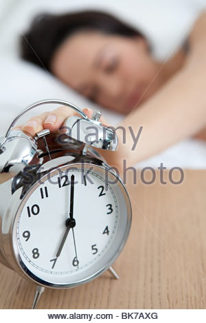 Woman reaching out for alarm clock - Stock Photo