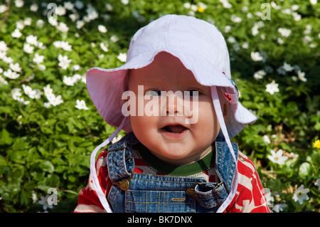 Portrait of a little girl in a sea of forest anemones in Dalby Soderskog National Park, Skane, Sweden