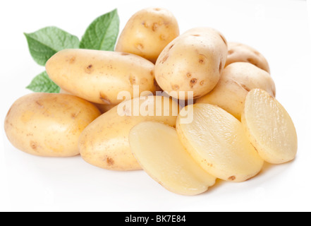 Yellow potatoes with leaves on a white background - Stock Photo