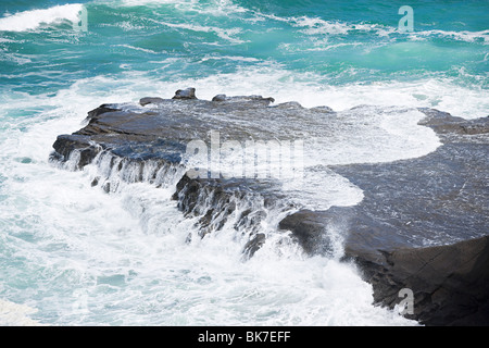 Auckland, surf washing over rocks at Muriwai Beach - Stock Photo