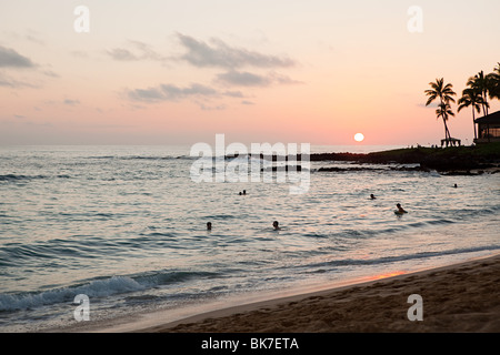 People in sea at sunset - Stock Photo