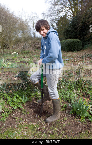 Model released teenage boy digging hole in garden - Stock Photo