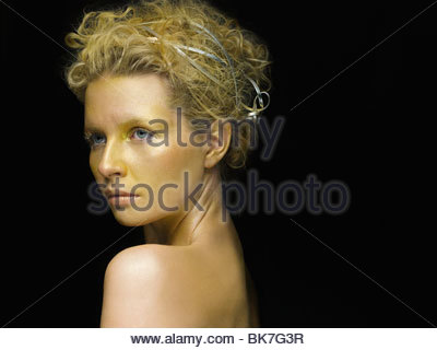Young woman covered in gold make up - Stock Photo