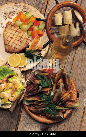 Grilled tuna, shrimp, mussels, and white wine on wood planks with ships wheel. - Stock Photo