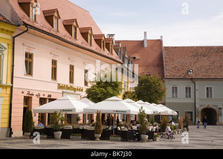 Old buildings and street cafe in historic city centre of Hermannstadt, Piata Mare, Sibiu, Transylvania, Romania, - Stock Photo