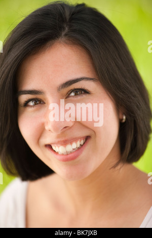 portait of a beautiful, young Hispanic woman in a grassy meadow - Stock Photo