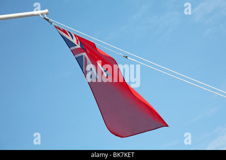 Union jack flag blowing in the wind on top of pole - Stock Photo