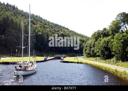 Yacht approaching lock, Crinan Canal, Highlands, Scotland, United Kingdom, Europe - Stock Photo