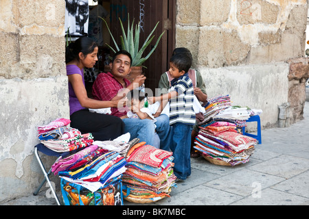 happy young Mexican family with baby & small boy selling textiles on the sidewalk on Calle Macedonio Alcala In Oaxaca - Stock Photo