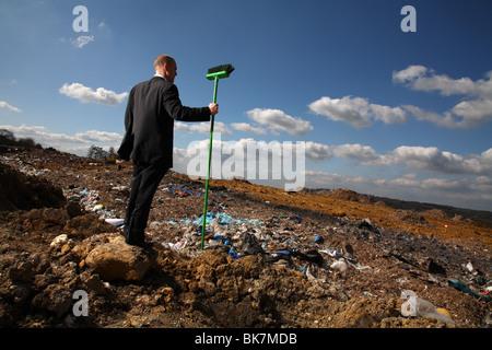 Businessman at british landfill site - Stock Photo
