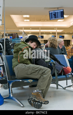 Man sleeping on an airport seat while is flight is canceled - Stock Photo