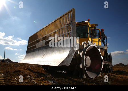 Earth mover on landfill site - Stock Photo
