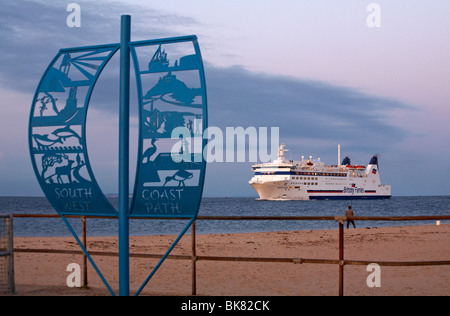 South West Coast Path sign at Studland, Dorset, UK with Brittany Ferries ferry Barfleur returning to Poole Harbour - Stock Photo