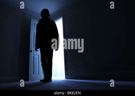 Silhouette of a male entering a dark room with a shaft of light behind