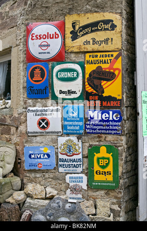 Old enamel advertising signs on a wall in Germany. - Stock Photo