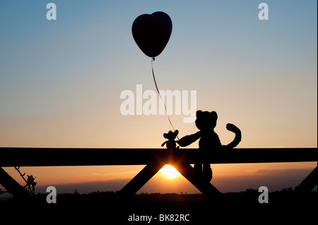 Cat and mouse soft toys holding a heart shape balloon in friendship, sitting on a gate at sunset. Silhouette - Stock Photo