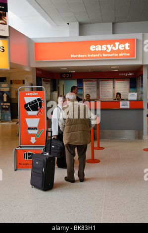 Passengers queuing at an Easyjet ticket desk - Stock Photo
