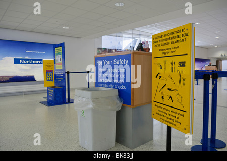 Signs at approach to airport security, warning passengers about prohibited items. - Stock Photo