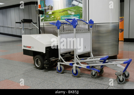 Small electric tractor unit for collecting and moving trolleys at an airport - Stock Photo