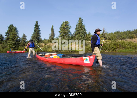 Two men lining canoe, walking bare feet in shallow Caribou Creek, upper Liard River, Yukon Territory, Canada - Stock Photo