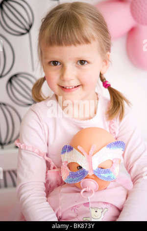 Girl in her bedroom playing with a doll - Stock Photo