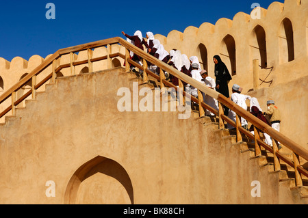 Schoolchildren on a field trip climbing the stairs to the battlements of the Castle of Nizwa, Sultanate of Oman, - Stock Photo