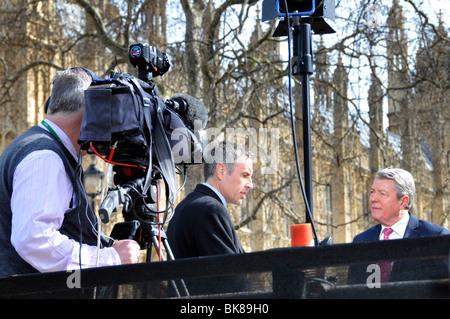 Sky News TV presenter Dermot Murnaghan interviewing Home Secretary Alan Johnson on podium outside Parliament - Stock Photo