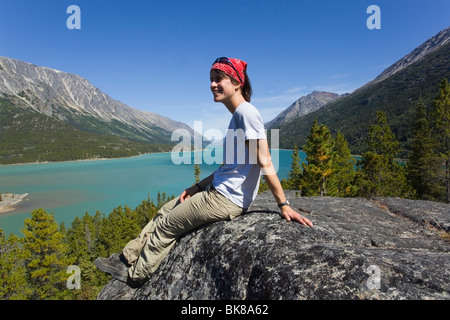 Young woman, hiker, backpacker sitting on rock, resting, enjoying panorama over Lake Bennett, historic Chilkoot - Stock Photo