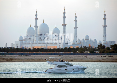 A luxury motor boat cruising past the Sheikh Zayed Grand Mosque in Abu Dhabi, capital of the United Arab Emirates. - Stock Photo