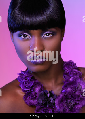 Beautiful young black woman headshot with makeup and background in purple colors. Beauty headshot. - Stock Photo