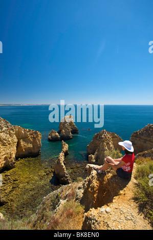 Woman with a view to Ponta da Piedade, Algarve, Portugal, Europe - Stock Photo