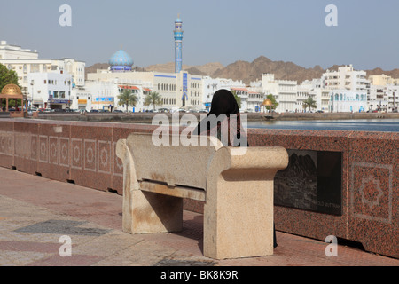 Omani woman sitting on bench at the Corniche of Muttrah, Sultanate of Oman. Photo by Willy Matheisl - Stock Photo