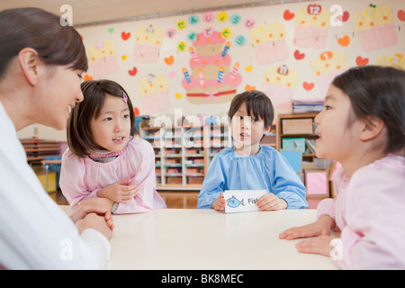 Kindergarten Teacher Teaching Children - Stock Photo