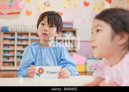 Kindergarten Boy Holding Picture Card - Stock Photo