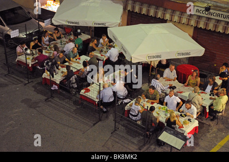 People sitting at outside café bar tables on pavement waiting for service for evening meal in Como Italy with TUBORG - Stock Photo