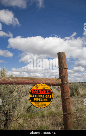 A caution sign on a barbed wire fence warns visitors about a Trans Canada Natural gas pipeline buried nearby, near - Stock Photo