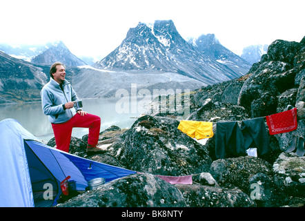 Photographer H. Mark Weidman drying out wet clothing on a backpacking trip in Auyuittuq National Park, Nunavut, - Stock Photo