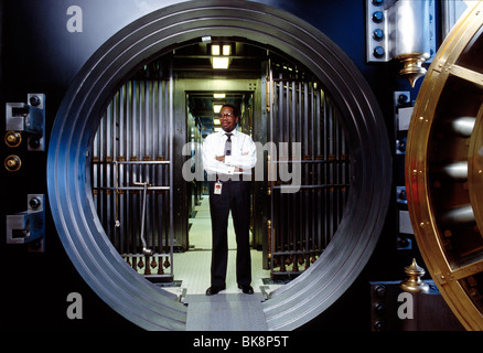 African American bank employee standing in the secure doorway to a large vault - Stock Photo