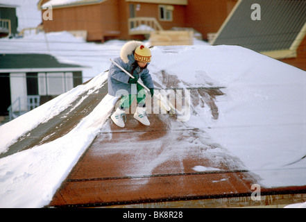 Inuit girl sweeping snow from the roof of her house in Lake Harbour, Baffin Island, Nunavut, Canada - Stock Photo