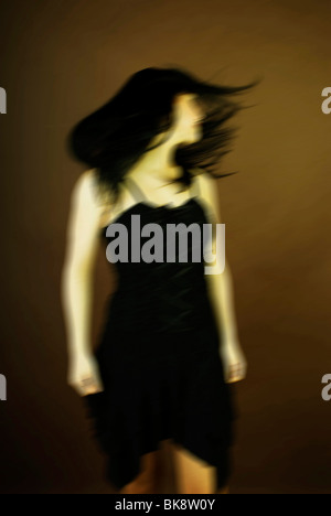 Dark-haired woman tossing her hair, movement - Stock Photo