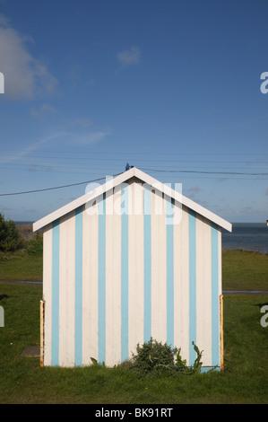Blue and white striped beach hut at Westward Ho, Devon, UK - Stock Photo